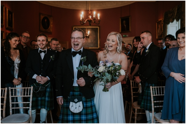bride laughing as her dads walks her down the aisle at winton castle