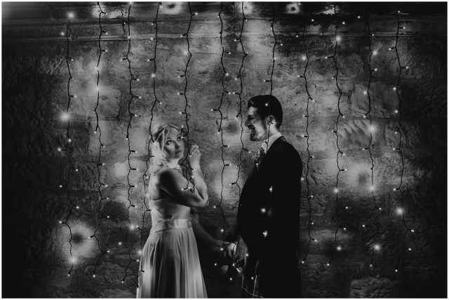 bride and groom in fairy lights at their wedding at winton castle