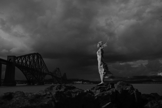 bride standing in beautful light near the forth bridge before her wedding at Dundas castle