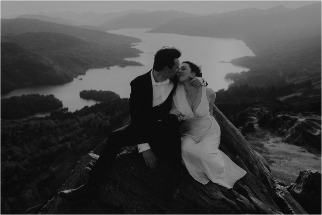 Bride and groom kiss on a mountain top in Scotland during their elopement