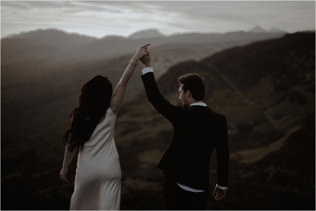 couple hold hands on Ben A'an during their scottish elopement
